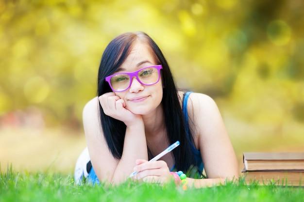 Ragazza teenager con il taccuino nel parco.