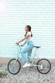 Ragazza teenager con la bicicletta d'annata alla porta esterna.
