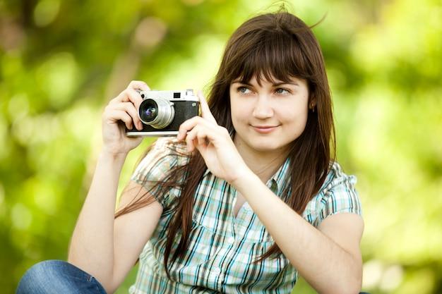 Ragazza teenager con la macchina fotografica al parco verde.
