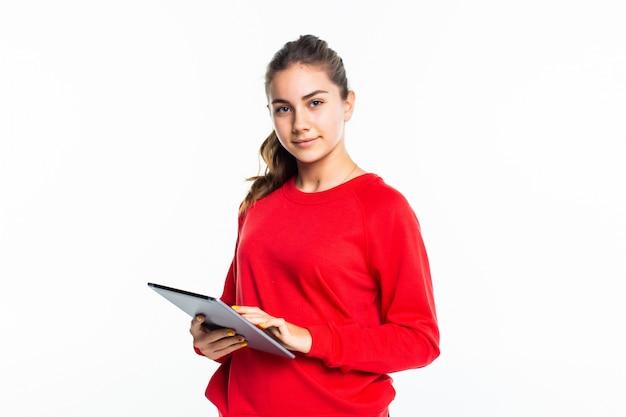 Ragazza teenager di bellezza felice che manda un sms su una compressa su una parete bianca