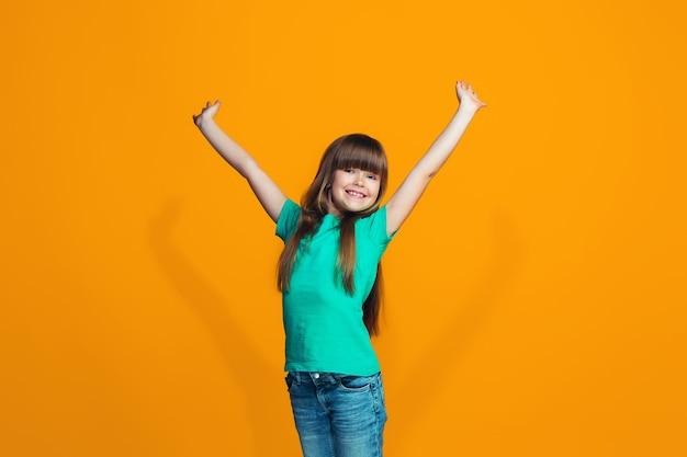 Ragazza teenager di successo felice che celebra essere un vincitore. immagine energica dinamica del modello femminile