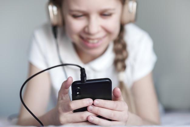 Ragazza teenager felice che parla con amici tramite video chat e che si siede a casa nella quarantena, coronavirus, concetto di comunicazione