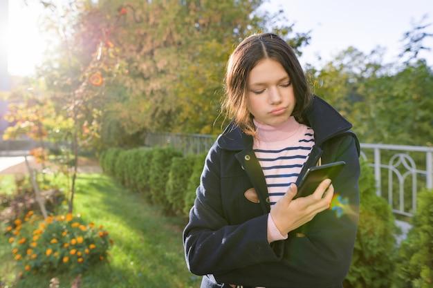 Ragazza teenager in cappotto facendo uso dello smartphone, giorno soleggiato di autunno