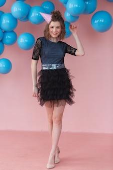 Ragazza teenager nel cono di compleanno in posa sul muro rosa e sullo sfondo di palloncini blu.