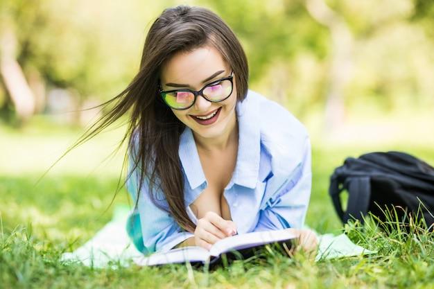 Ragazza teenager sognante sorridente che si trova sull'erba nel parco con il taccuino