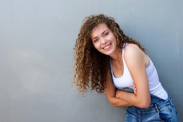 Ragazza teenager spensierata felice che si appoggia con le braccia attraversate