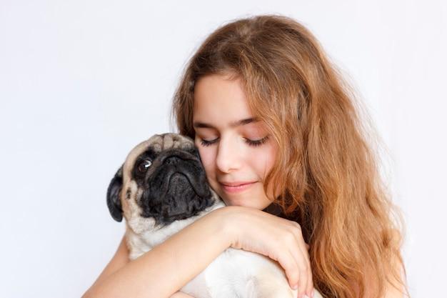 Ragazza teenager sveglia che abbraccia e che bacia un cane del carlino su fondo bianco