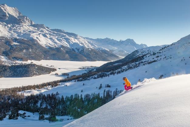 Ragazza telemark sciatore sul pendio sopra la valle dei laghi