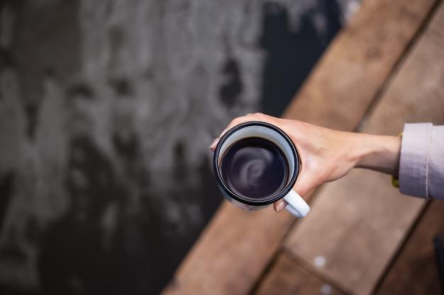 Ragazza tiene una tazza di caffè in metallo nelle sue mani vicino al lago mentre era seduto su un molo in legno.