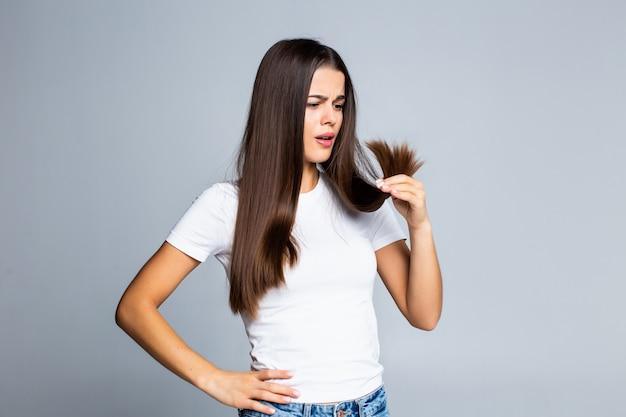 Ragazza triste che esamina i suoi capelli nocivi isolati su bianco