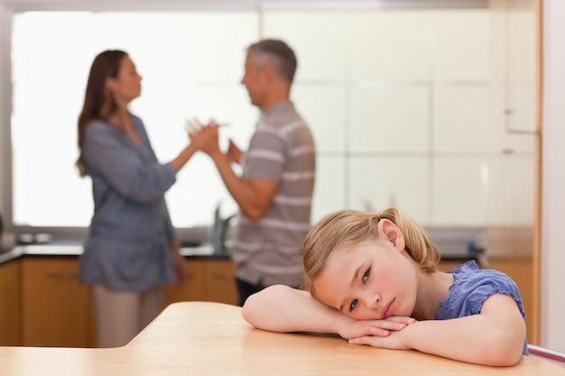 Ragazza triste che sente i suoi genitori che discutono