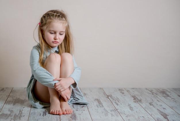 Ragazza triste che si siede da solo sul pavimento