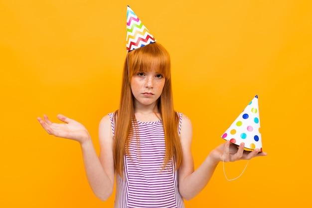 Ragazza triste dai capelli rossi con una protezione di festa alla macchina fotografica su un giallo