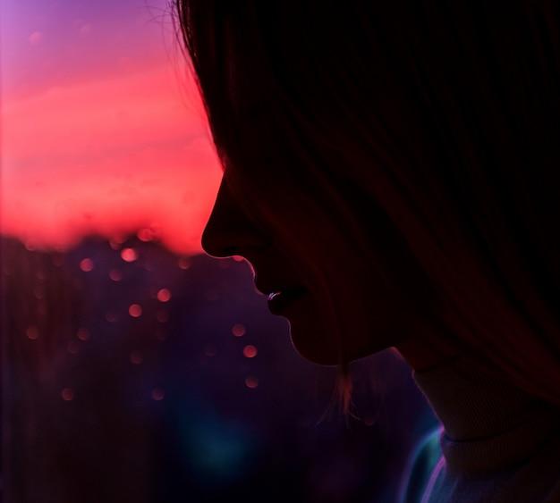 Ragazza triste dalla finestra contro il tramonto con la pioggia