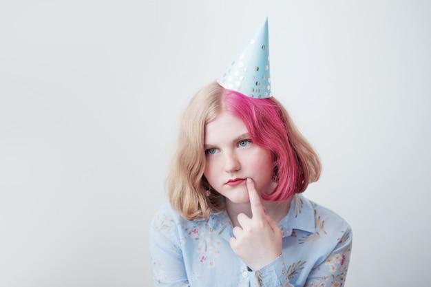 Ragazza triste dell'adolescente in cappello di compleanno