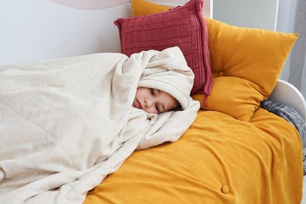 Ragazza triste sveglia a letto avvolta in coperta molle