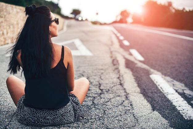 Ragazza turistica abbastanza castana che si siede sulla strada