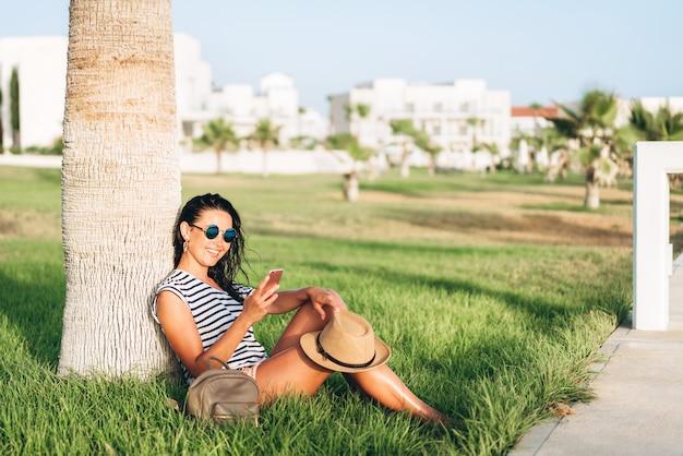 Ragazza turistica asiatica della vaschetta graziosa che si siede sotto la palma e che per mezzo del suo smart phone.