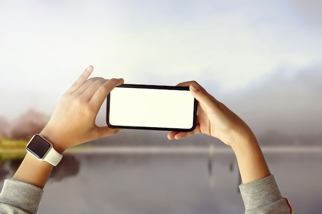 Ragazza turistica che cattura foto con il telefono cellulare sul bellissimo paesaggio