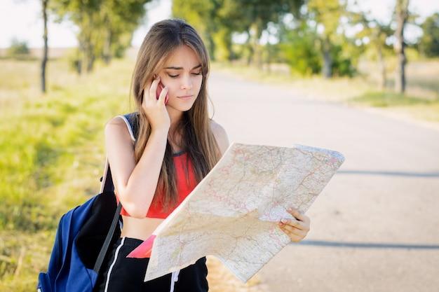 Ragazza turistica in cerca di direzione sulla mappa e chiedere aiuto. la giovane viaggiatore si è persa in campagna la sera e chiama gli amici per chiedere aiuto