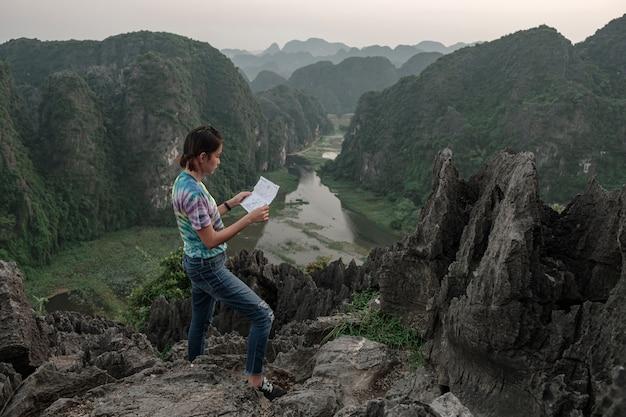 Ragazza turistica mappa permanente di vista del picco sulla montagna