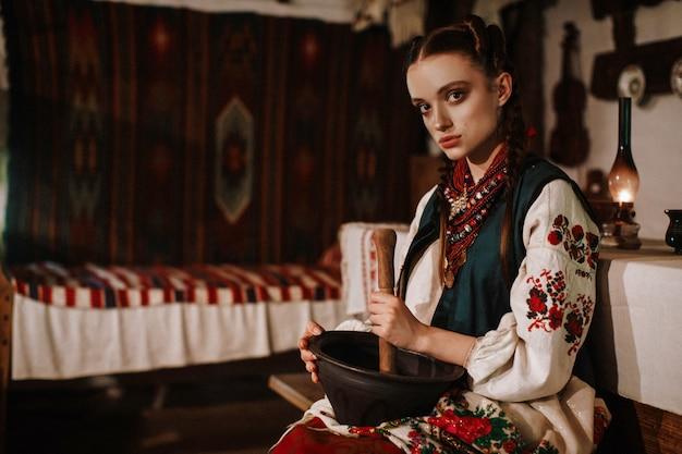 Ragazza ucraina affascinante in un vestito tradizionale che cucina nella cucina tradizionale
