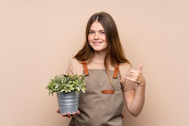 Ragazza ucraina del giardiniere dell'adolescente che tiene una pianta che fa gesto del telefono