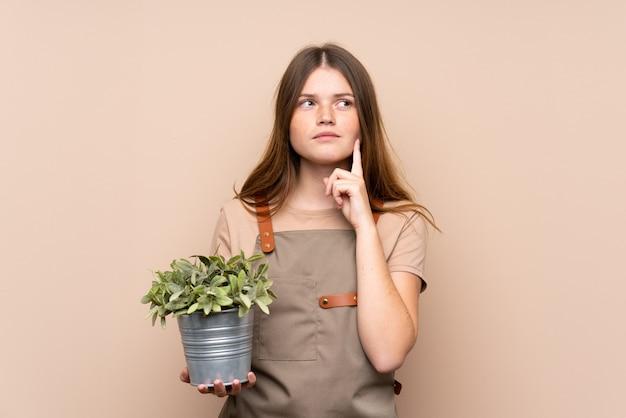 Ragazza ucraina del giardiniere dell'adolescente che tiene una pianta che pensa un'idea