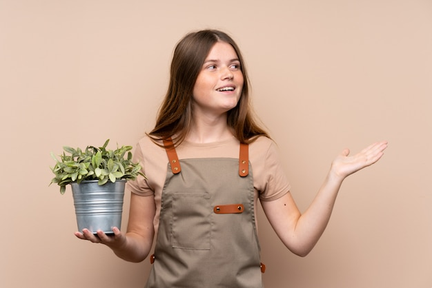 Ragazza ucraina del giardiniere dell'adolescente che tiene una pianta con espressione facciale di sorpresa