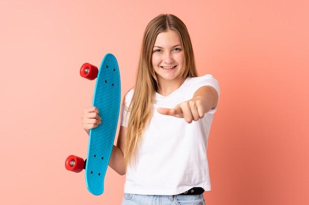 Ragazza ucraina del pattinatore dell'adolescente isolata sul rosa con un pattino e che indica la parte anteriore