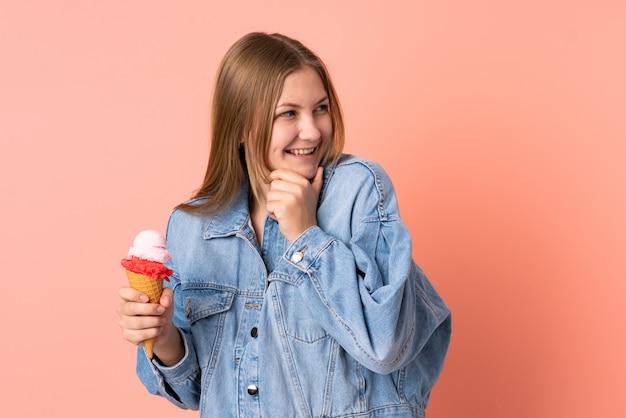 Ragazza ucraina dell'adolescente con un gelato della cornetta isolato sul rosa che pensa un'idea e che guarda lato