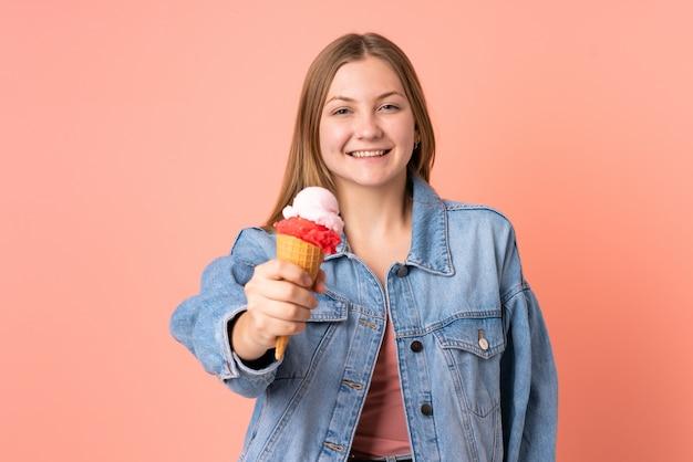 Ragazza ucraina dell'adolescente con un gelato della cornetta isolato sul rosa con l'espressione felice