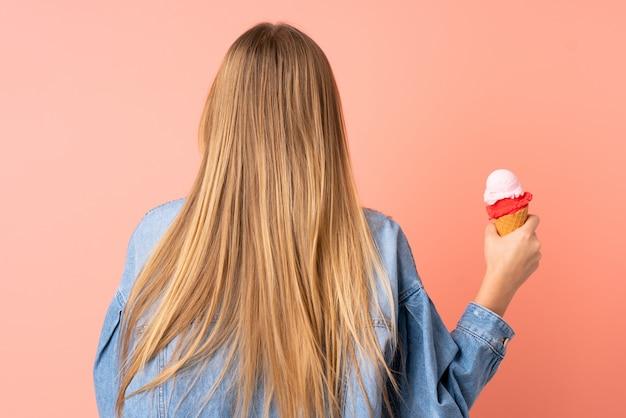 Ragazza ucraina dell'adolescente con un gelato della cornetta isolato sul rosa nella posizione posteriore