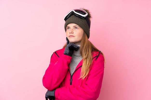 Ragazza ucraina dello sciatore dell'adolescente con i vetri di snowboard sopra il pensiero isolato un'idea
