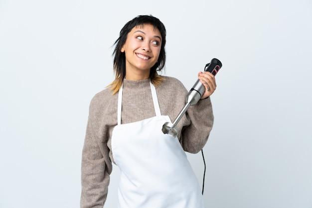 Ragazza uruguaiana del cuoco unico che usando il miscelatore della mano sopra la parete bianca che ride e che osserva in su