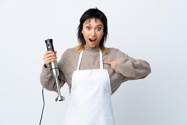 Ragazza uruguaiana del cuoco unico che usando il miscelatore della mano sopra la parete bianca con espressione facciale di sorpresa