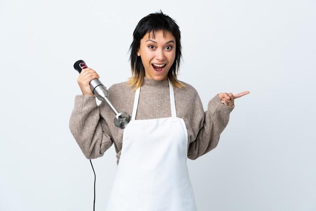 Ragazza uruguaiana del cuoco unico che usando il miscelatore della mano sopra la parete bianca sorpresa e indicando dito il lato