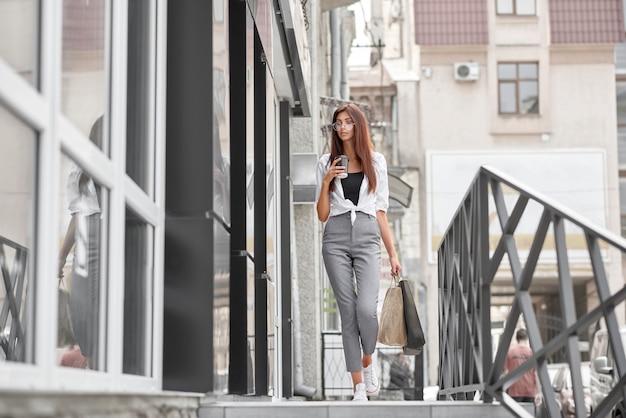 Ragazza vestita alla moda che cammina fuori dal negozio sulla strada. portando i sacchetti di carta
