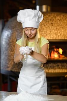 Ragazza vestita da cuoco che sparge la farina