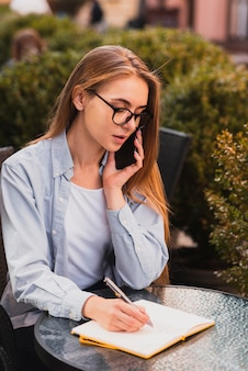 Ragazza vestita ufficio che parla sul telefono