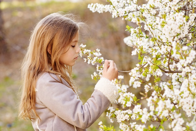 Ragazza vicino al ciliegio in fiore