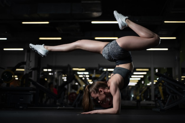 Ragazza yogi che fa inversione avanzata e hand-balance scorpion handstand.