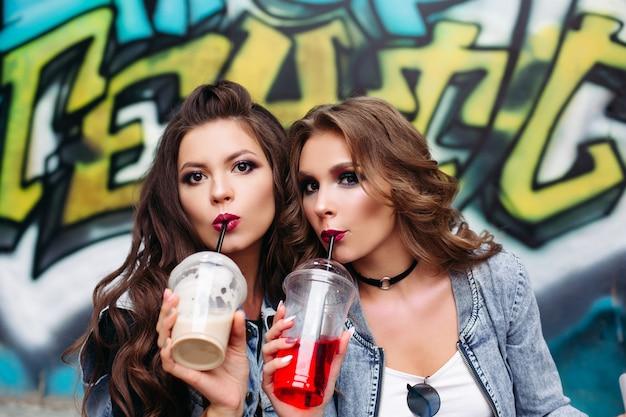 Ragazze abbastanza teenager con trucco e acconciatura che bevono limonata da asporto sopra i graffiti.