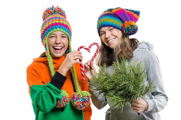 Ragazze adolescenti divertendosi con bastoncini di zucchero di natale