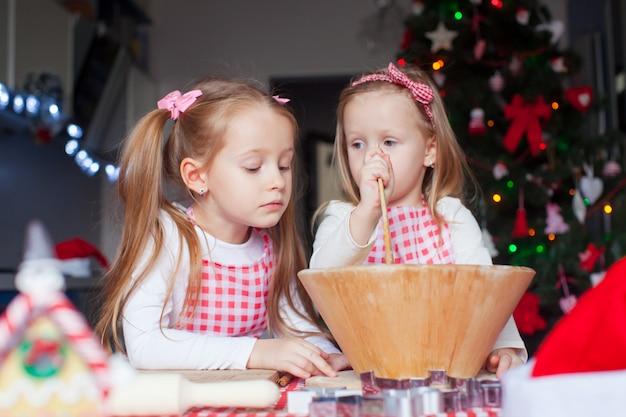 Ragazze adorabili che cuociono i biscotti del pan di zenzero per la cucina di natale a casa
