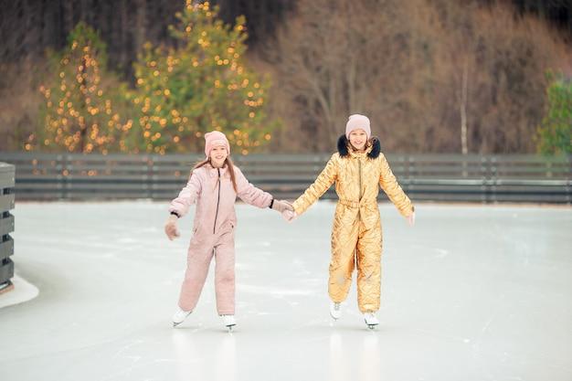 Ragazze adorabili che pattinano sulla pista di pattinaggio sul ghiaccio all'aperto nel giorno della neve di inverno