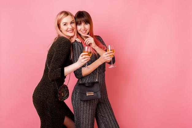 Ragazze alla moda con bicchieri di bevande alcoliche in posa sulla parete rosa chiaro