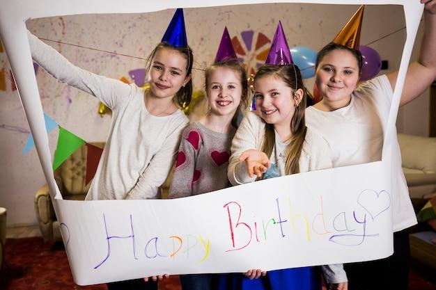 Ragazze allegre con segno di compleanno