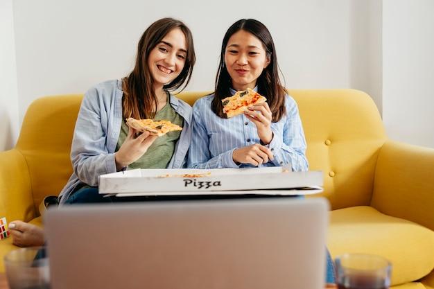 Ragazze allegre mangiando pizza e guardando commedia