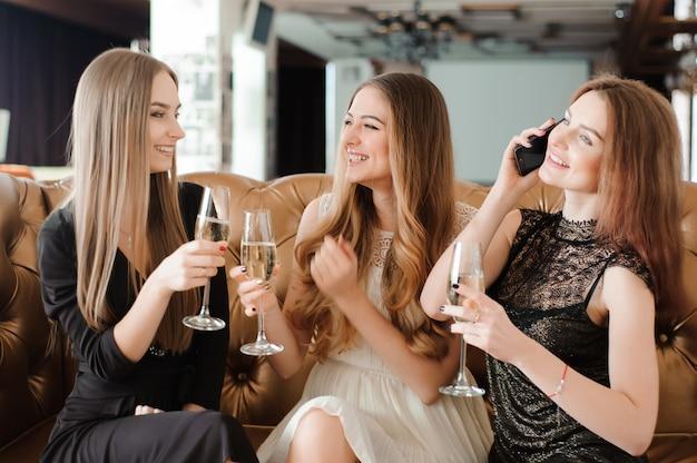 Ragazze allegre tintinnio di bicchieri di champagne alla festa